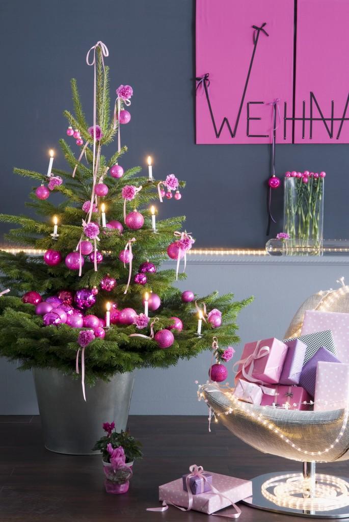 Geschmückter Weihnachtsbaum mit pinkfarbenen Kugeln neben Sessel mit Geschenken vor grauer Wand und Weihnachtsgruss an pinkfaben